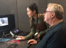 Carol Yan Li leans next to Academy Award winning Sound dEsigner Tom Fleischman as they both sit at our state of the art editing system looking at the screen.