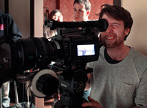 A person looks through the viewfinder of a big digital film camera while two people stand behind them looking at what the camera is filming.
