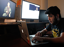A person sitting down in the SVA editing lap working on a laptop with monitors behind them.