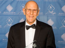 Profile photo of faculty member Chris Newman wearing a spiffy tux and holding an award with a banner for an awards ceremony behind him, smiling looking directly into the camera.