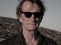 Profile photo of faculty member Ed Bowes standing outside with sunglasses on and a button up shirt with the collar unbuttoned looking directly into the camera.