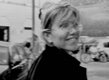 Profile photo of faculty member Simona Migliotti Auerbach in black and white wearing a dark coat outside with her back to the camera and head turned to the right looking at the camera smiling.