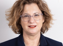Profile photo of faculty member Kerry Fulton looking directly into the camera with a dark blazer over a dark shirt and a silver colored necklace and clear glasses.