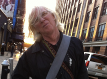 Profile photo of faculty member Bill Hopkins taken outside a busy street. A bag strap hangs across his black jacket as he looks into the camera with a sun setting behind him.