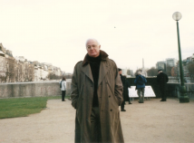 Profile photo of faculty member David Black in an olive trench coat and black shirt standing outside in front of a pond with a group of people behind him.