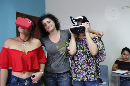 Alessandra Zeka stands in the middle of two people, her arms affectionately around both of them. The two people on either side of Alessandra are both in the midst of using the occulous VR headset, looking in different directions as they experience the virtual reality.