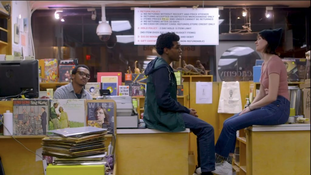 Lanre sits in a book store looking bored while two patrons sit on the counter conversing, seeming to pay him no mind.
