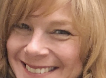 Stacy Herman smiles at the camera in a close up that only shows her face and her long blonde hair.