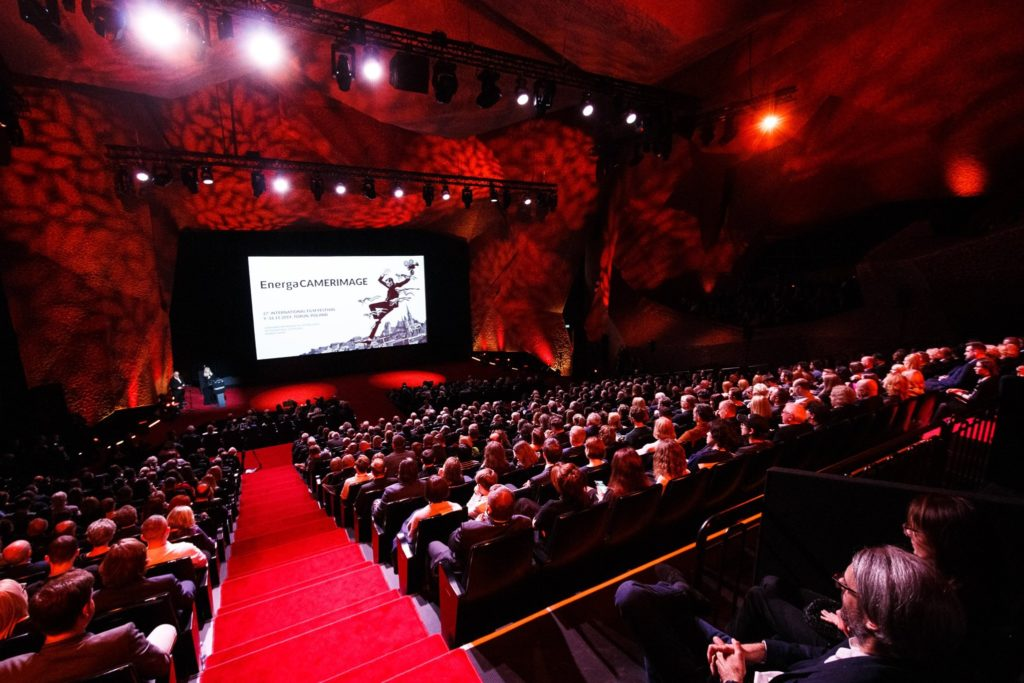 """A packed auditorium of people sitting watching the screen that has the word """"energaCameraimage"""" on it. The auditorium is all red."""