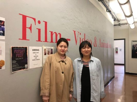 """Jungyoon Jang & Hae Seoung Kim stand in the hallway of the SVA main building in front of the words """"Film - Video & Animation"""" written on the walls."""