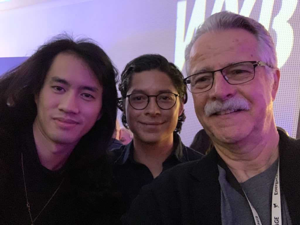 Three people pose for a group selfie. The two on the right both have glasses.