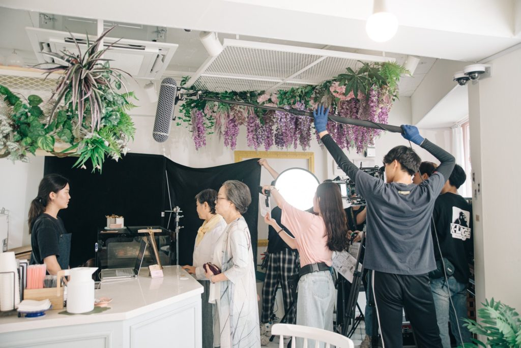 Behind the scenes of a a shoot in process. A person stands at a cafe counter looking at the cashier while a film crew stands to the side filming them.