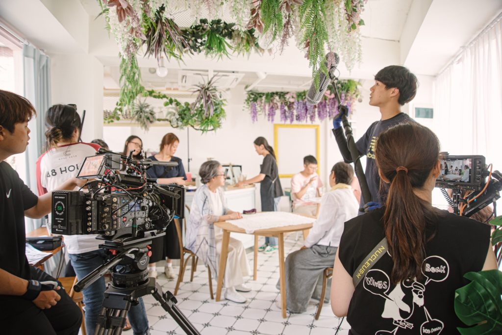 Behind the scenes shot of SVA students  Jungyoon Jang & Hae Seoung Kim film. A person with a camera films restaurant patrons eating inside an all white cafe that has hanging plants decorating the ceiling. a person with a boom pole stands to the side while another person holds a viewfinder on the right..