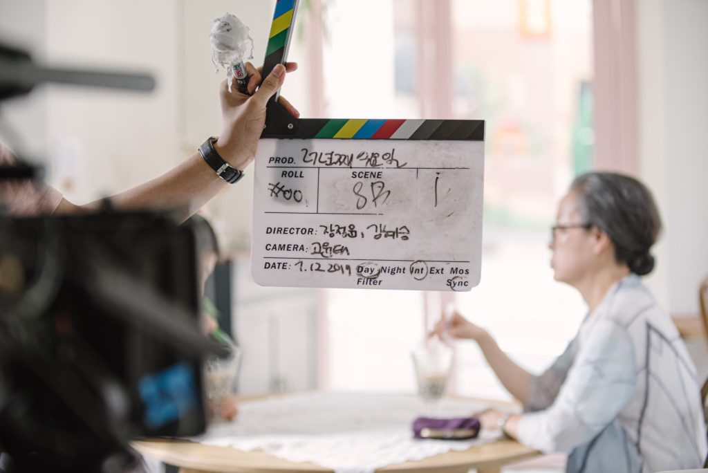 A hand holds a camera slate ready to clap before filming beings. Behind it, an actor sits at a table slightly out of focus.