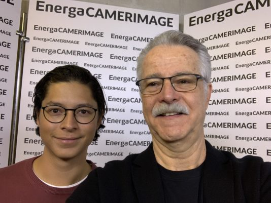 Two people (Alejandro Cortes & Dejan Georgevich) with glasses stand in front of a white fixture with the words EnergaCAMERAIMAGE on it.