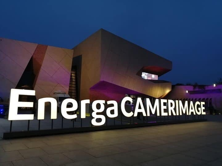 """A building with the word """"EnergaCAMERAIMAGE"""" in big letters as a sign outside of it. Purple lights shine on the building and the photo has been taken at dusk."""