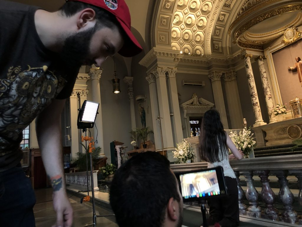 Behind the scnes of a shoot in a church. Two crew members set up a camera shot of a person praying to jesus