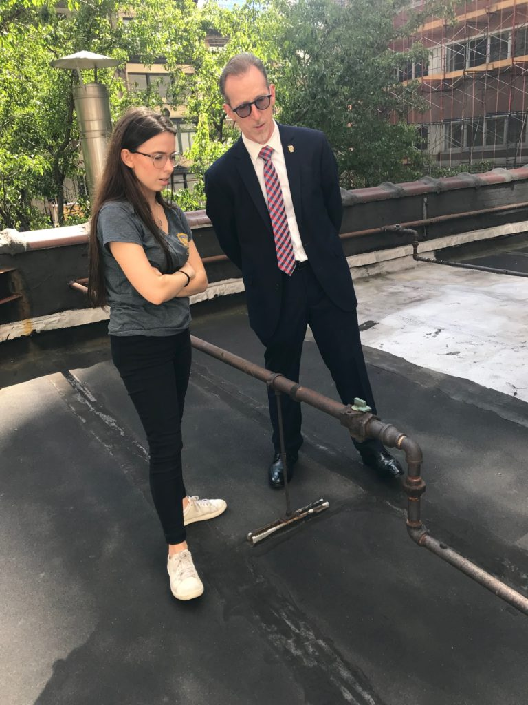 Julia Ward stands on a rooftop with an interview subject dressed in a suit and wearing glasses.