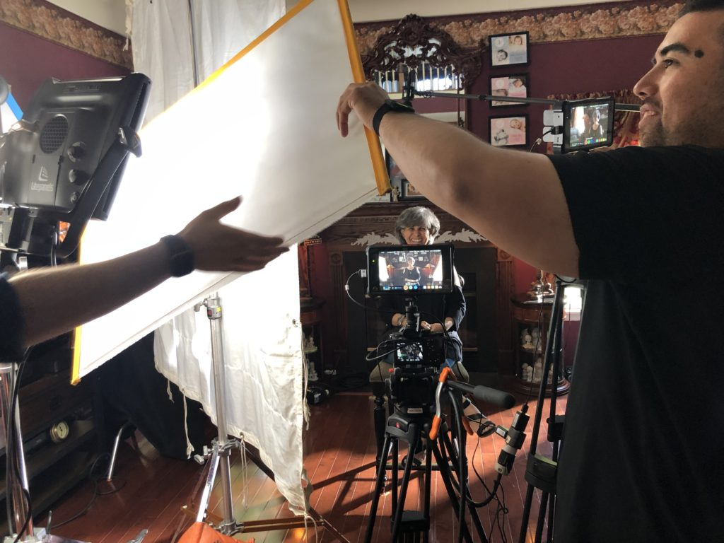 Behind the scenes of an interview. The interview subject sits in front of a camera smiling while two crewmembers set up a chimera lightbox