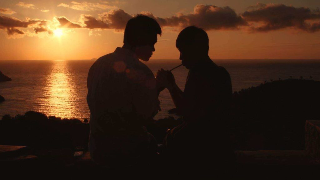 A man lights the cigarette for another man while they sit on the edge of a hill enjoying the sunset over a body of water.