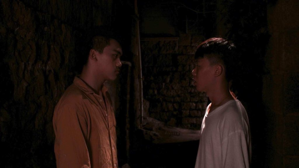 Two men stare intensely at each other, surrounded by blackness. One has a collared button up shirt on and the other a white t shirt.