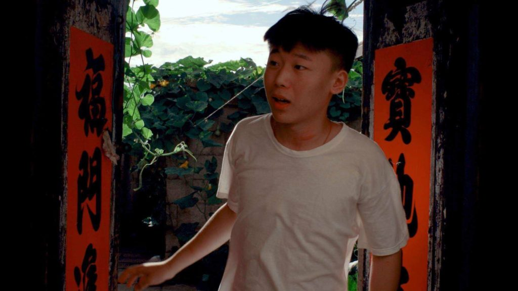 A man in a white shirt stands in the threshold of a doorway with chinese letters on the sides.