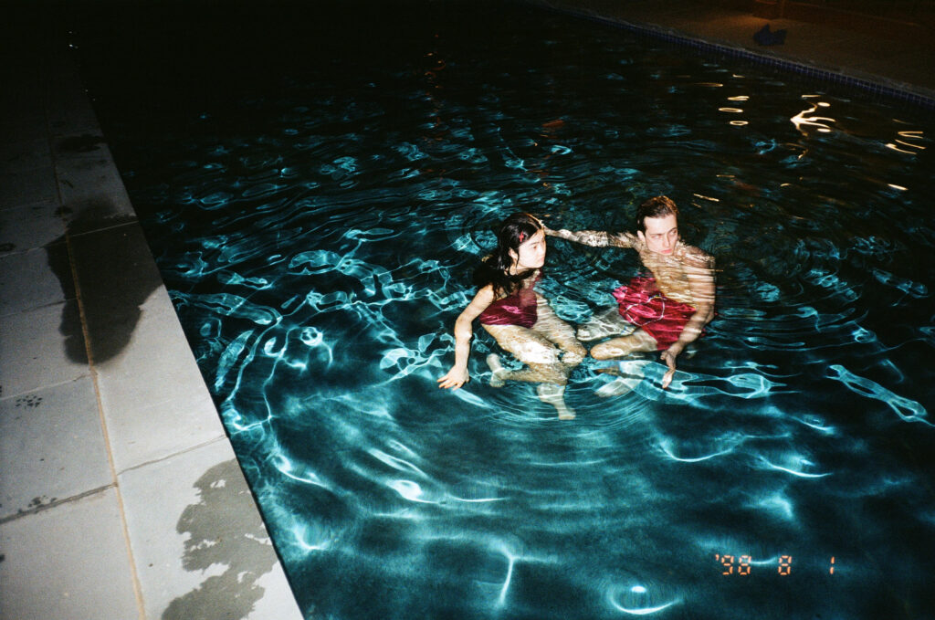 Two people standing in a shallow indoor pool. both wearing red bathing suits.