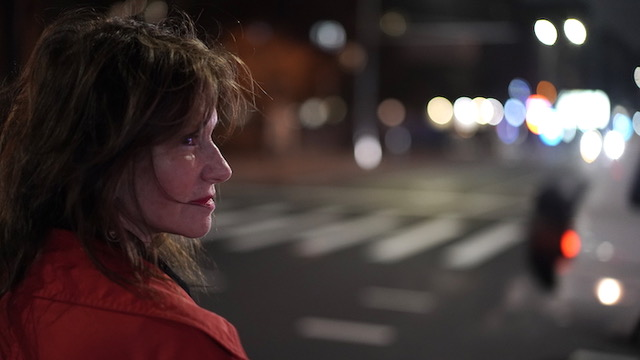 Still photo from Frank Vitale's film showing a person with long hair in a red jacket/coat with their head in profile in front of an out of focus city street.