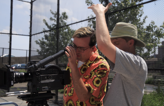 Behinds the scenes on Joe Ralkos film as he looks into a camera viewfinder and a crewmember stands behind him blocking the sun.