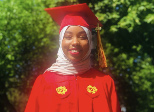 Recent graduate Hanaan Louis stands outside smiling with her SVA graduation cap and gown on.