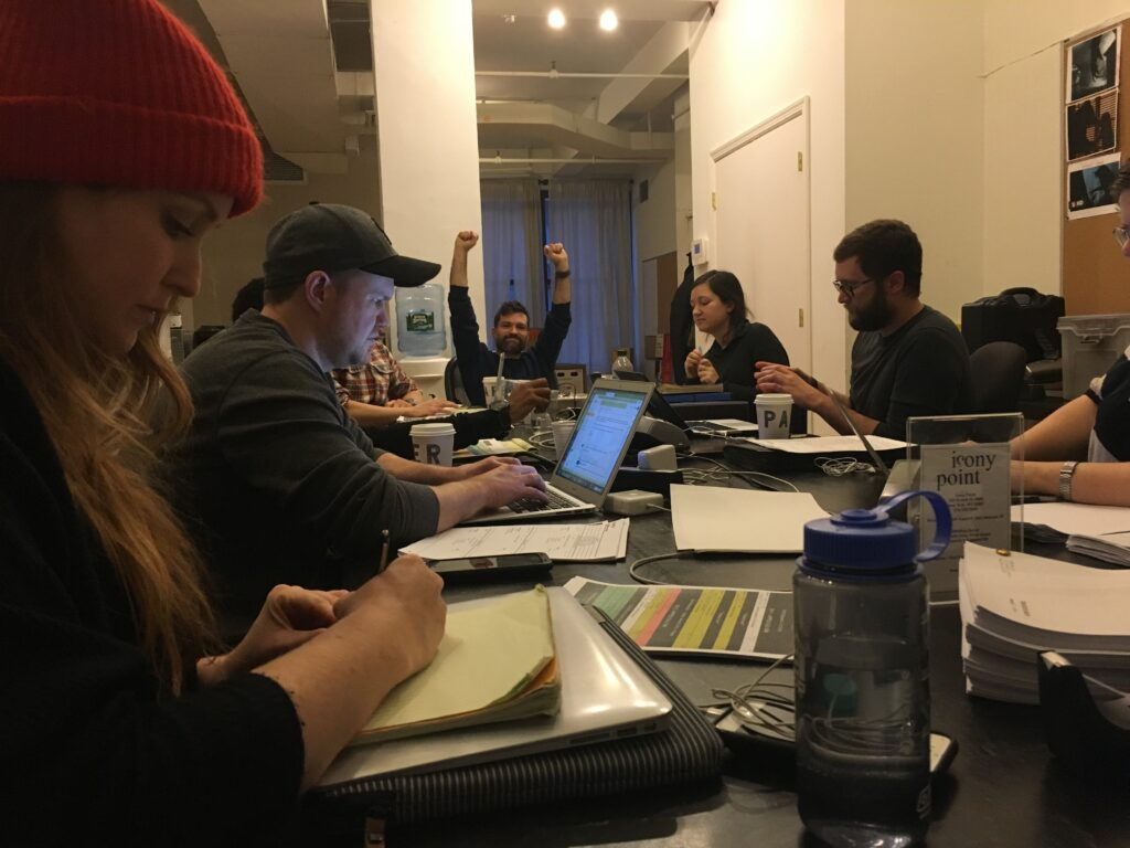 Pre poduction meeting at an office conference table. The preproduction crew gather around with their laptops and scripts all over the table. A person at the head of the table has their fists up in the air with a smile on his face.