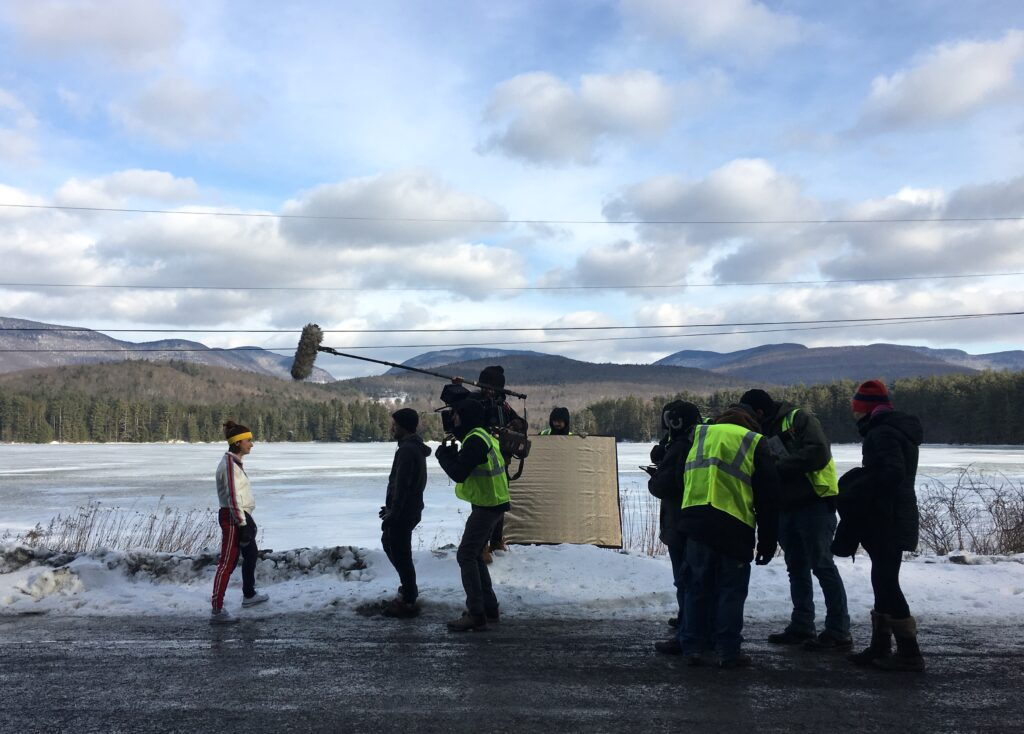 Outside in an open snowy field, actress Aya Cash is seen being filmed in her track suit mentioned above. A camera crew stands in front of her, filming.