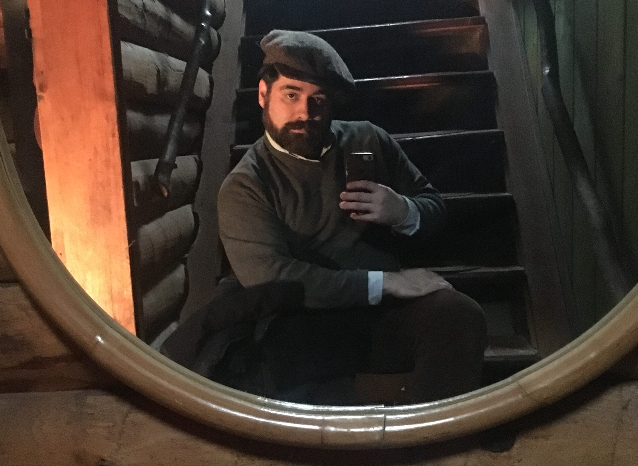 Sean Dermond taking a mirror selfie on set in front of a large oval mirror, wearing a hat and warm clothing.
