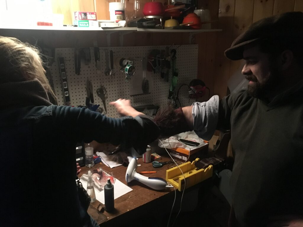 Sean Dermond working with Erica Pearce Hair and Make-Up adding blood to a werewolf arm.
