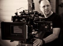 black and white photo of Faculty member Frank Prinzi standing in front of a large film camera, looking off to the side.