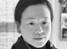 artful Black and white headshot of Kay Hung looking directly into the camera