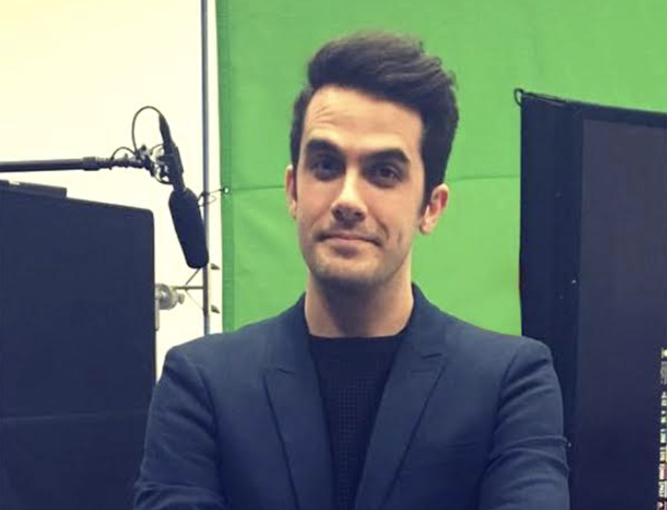 Will Henry looking directly into the camera wearing a sharp looking blazer with a background of film equipment (green screen, Boom microphone) behind him