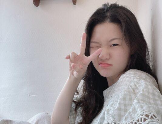 Selfie of Julie Jang winking at camera giving peace sign