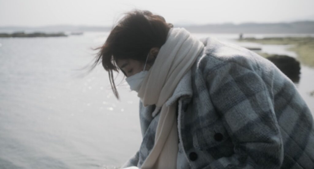 still image from Julies film of someone bending over with a scarf wrapped around their face protecting their mouth and nose